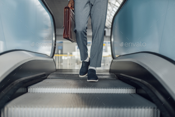 Black businessman descending on escalator in mall - Stock Photo - Images