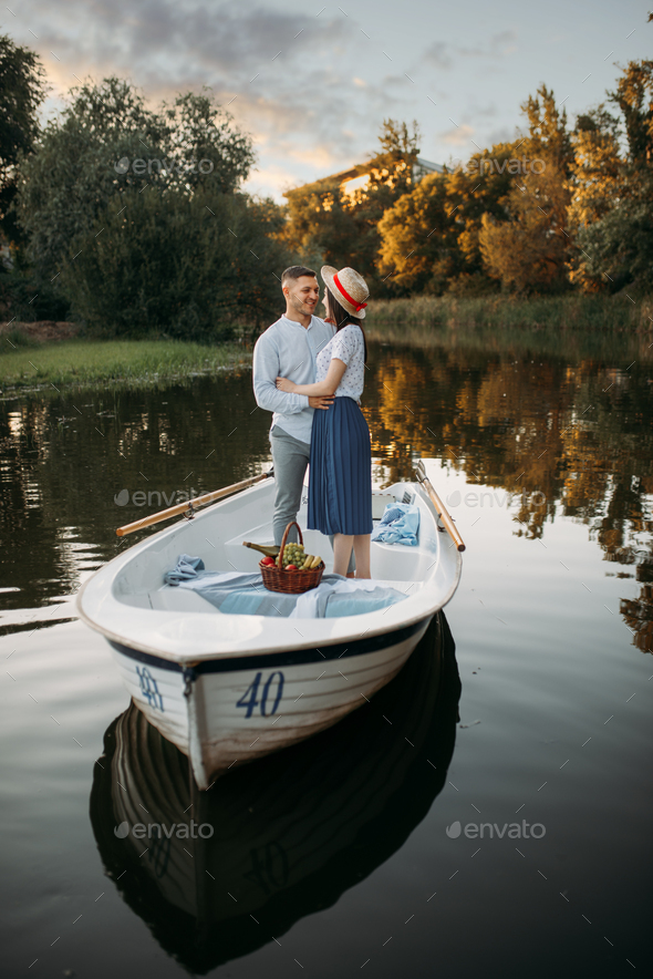 Love couple standing in a boat on quiet lake - Stock Photo - Images