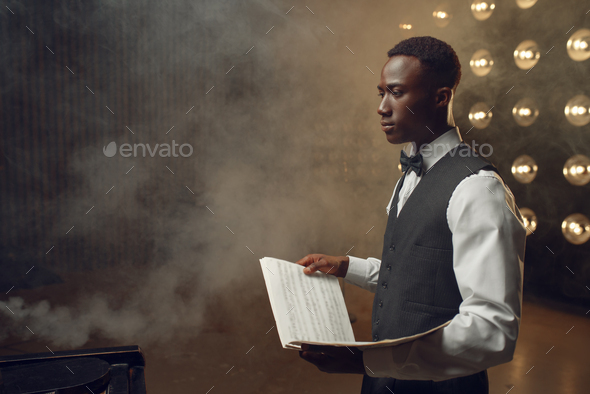 Black pianist with music notebook on the stage - Stock Photo - Images