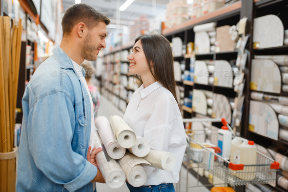 Couple choosing wallcovering in hardware store - Stock Photo - Images