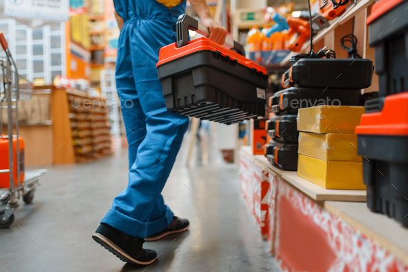 Builder with toolbox at the shelf, hardware store - Stock Photo - Images