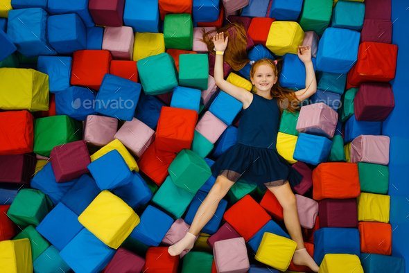 Cute little girl lying in soft cubes, playground - Stock Photo - Images