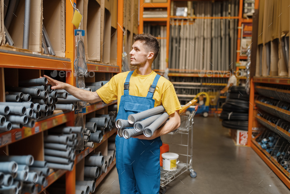 Male builder choosing piping in hardware store - Stock Photo - Images