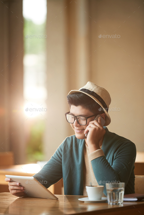 Cheerful man with gadgets in cafe - Stock Photo - Images