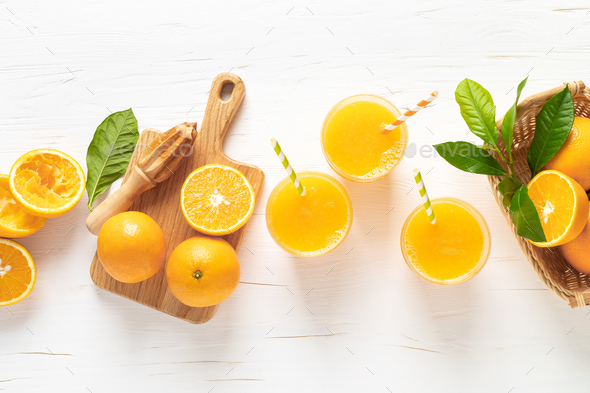 Orange juice. Freshly squeezed juice in glasses and fresh fruits with leaves, view from above - Stock Photo - Images