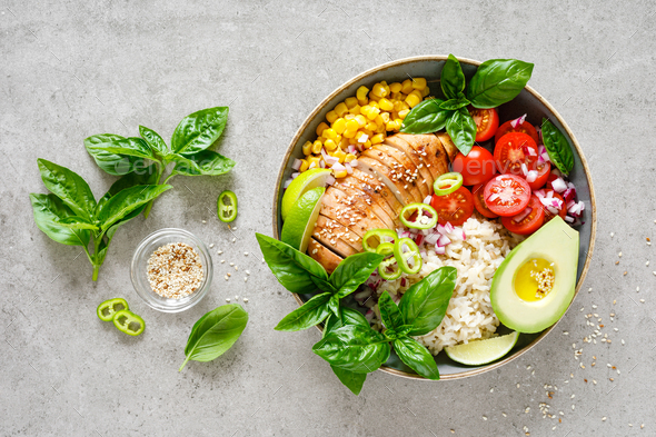Buddha lunch bowl with grilled chicken breast, tomato, onion, corn, avocado, basil salad and rice - Stock Photo - Images