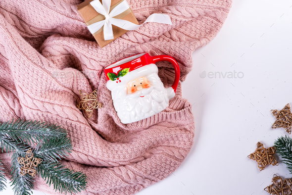 Pink knitted sweater with gift box, Santa's cup, christmas decoration and fir branches on a - Stock Photo - Images