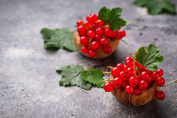 Ripe red currant berries in wooden bowls - Stock Photo - Images