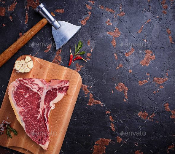 Raw T-bone steak with hatchet - Stock Photo - Images