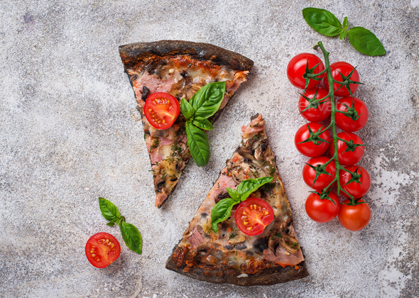 Pieces of  black pizza with tomatoes and basil - Stock Photo - Images