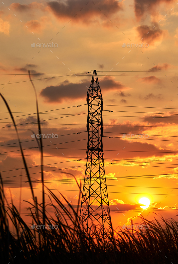 Silhouetted electricity pylons with the vivid sky of sunset - Stock Photo - Images