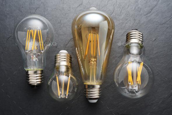 Transparent LED filament light bulbs on black background. - Stock Photo - Images