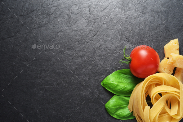 Fettuccine pasta with basil, tomato and cheese on black backgrou - Stock Photo - Images