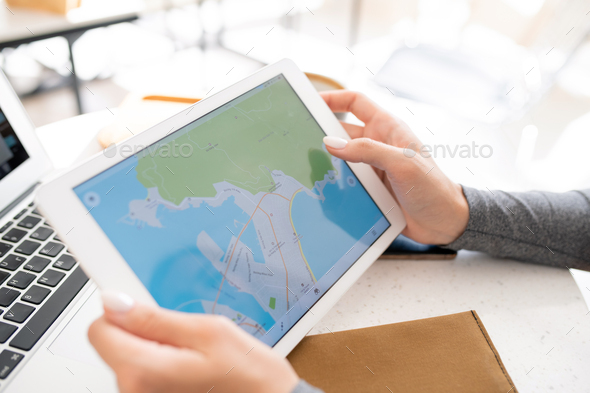 Hands of young female student holding digital tablet with map on display - Stock Photo - Images