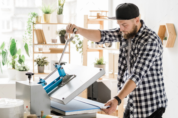 Craftsman using special equipment while printing decor on workpiece of collar - Stock Photo - Images