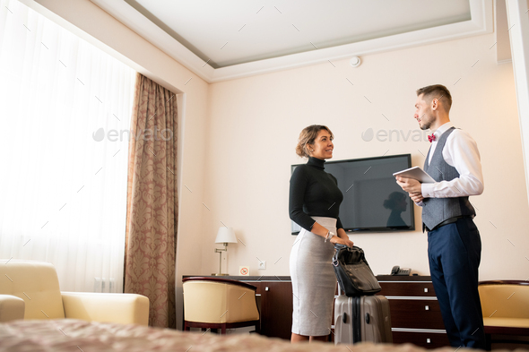 Young elegant porter with touchpad talking to pretty businesswoman with baggage - Stock Photo - Images