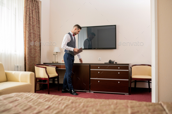 Young elegant hotel porter with touchpad touching piece of wooden furniture - Stock Photo - Images