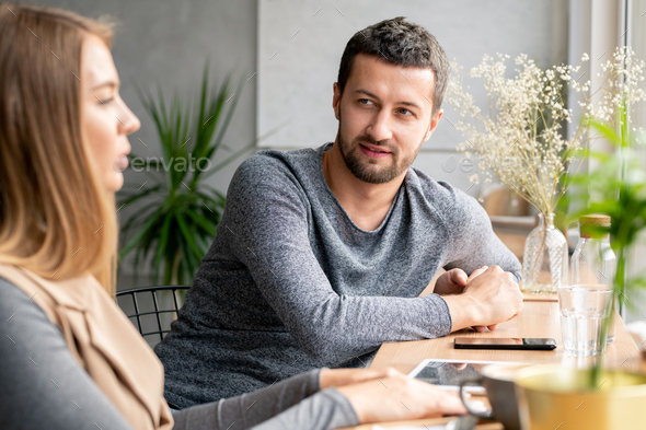 Young man in casual pullover looking at his girlfriend during conversation - Stock Photo - Images