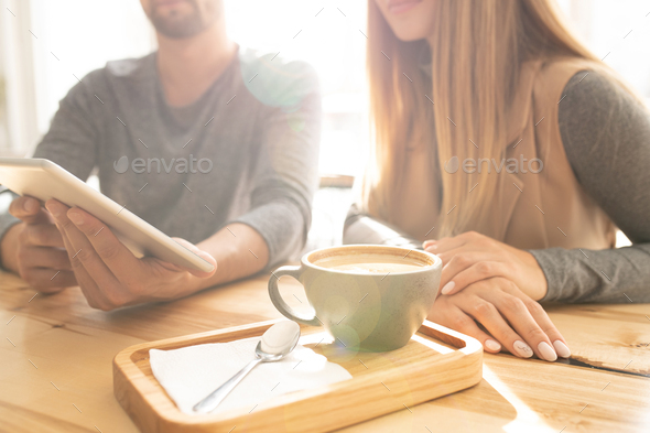 Cup of fresh cappuccino and spoon on wooden tray on background of young couple - Stock Photo - Images
