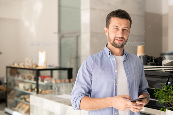 Handsome guy in casualwear scrolling in smartphone while looking at you - Stock Photo - Images