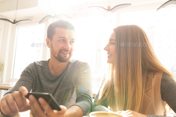 Happy young affectionate couple with smartphone discussing funny stuff in cafe - Stock Photo - Images