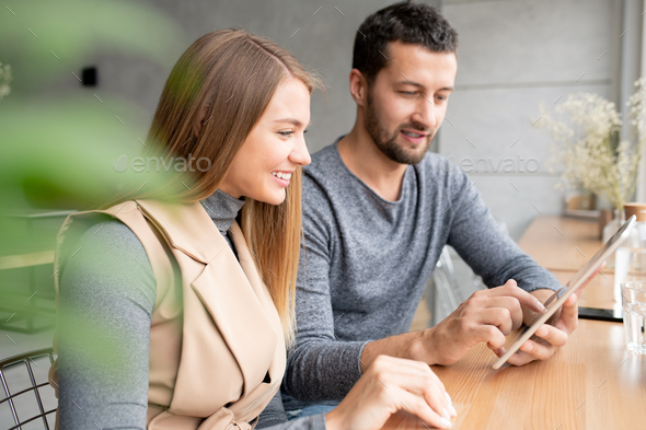Happy young businesswoman and her colleague preparing presentation at meeting - Stock Photo - Images