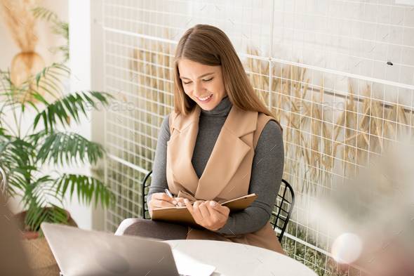 Student or businesswoman with notebook and pen making notes in front of laptop - Stock Photo - Images