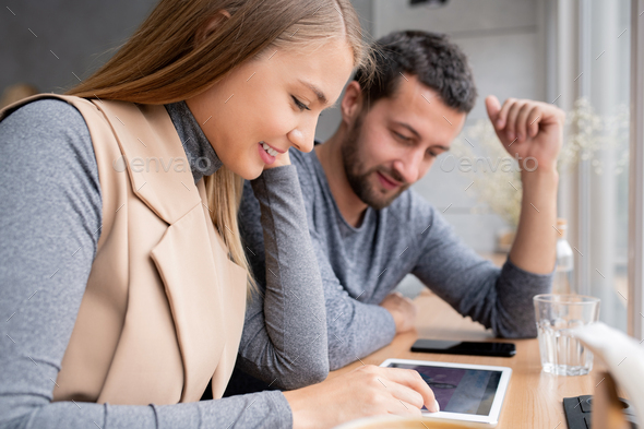 Happy girl and her boyfriend scrolling through black friday sale in touchpad - Stock Photo - Images