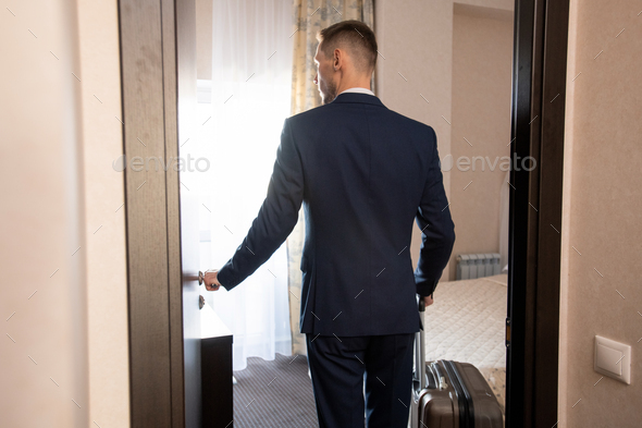 Back view of young elegant business traveler in formalwear entering hotel room - Stock Photo - Images