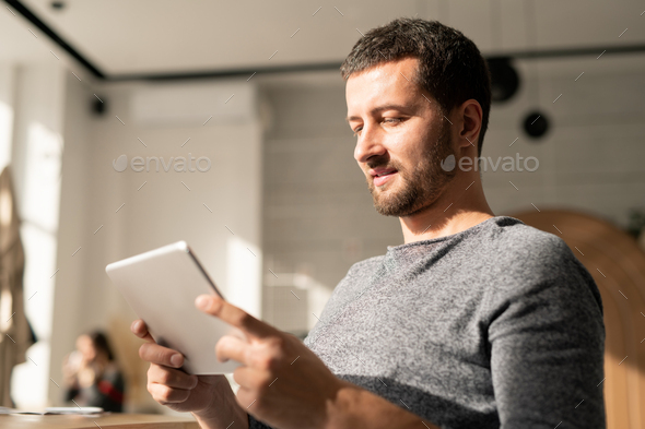 Casual young man with digital tablet communicating through video-chat - Stock Photo - Images
