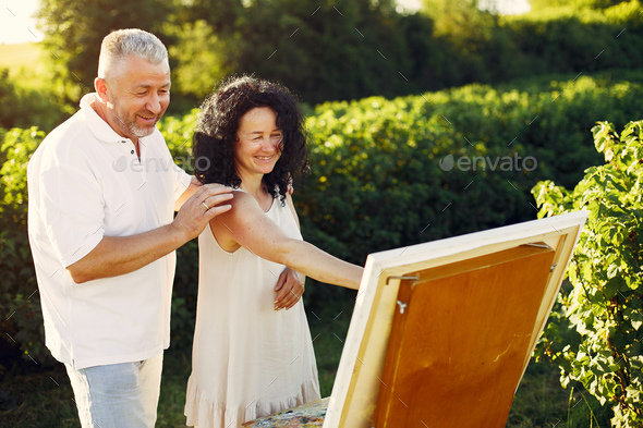 Beautiful adult couple drawing in a summer field - Stock Photo - Images