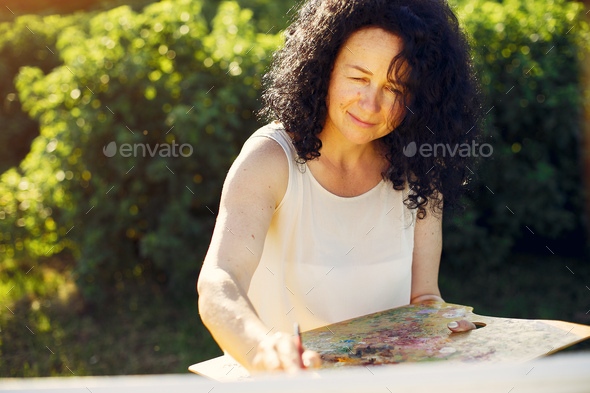 Beautiful adult woman drawing in a summer field - Stock Photo - Images