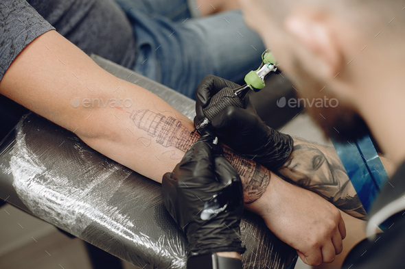 Man doing a tattoo in a tattoo salon - Stock Photo - Images