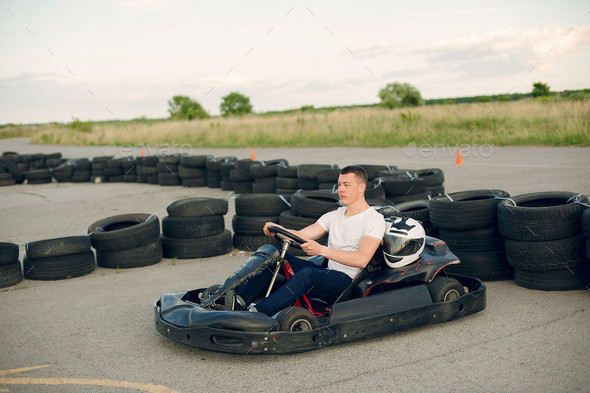 Handsome man in a karting with a car - Stock Photo - Images
