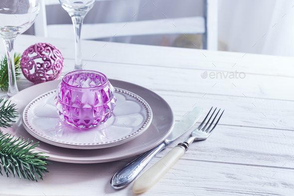 Place table setting for Christmas white table with purple decor elements with green branches - Stock Photo - Images
