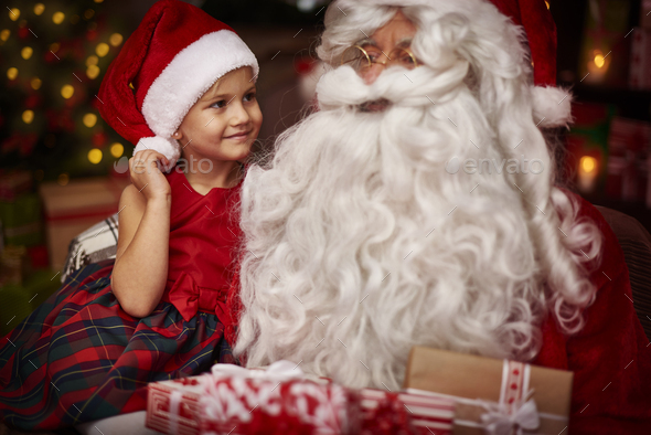 Cute girl sitting on the santa's knees - Stock Photo - Images