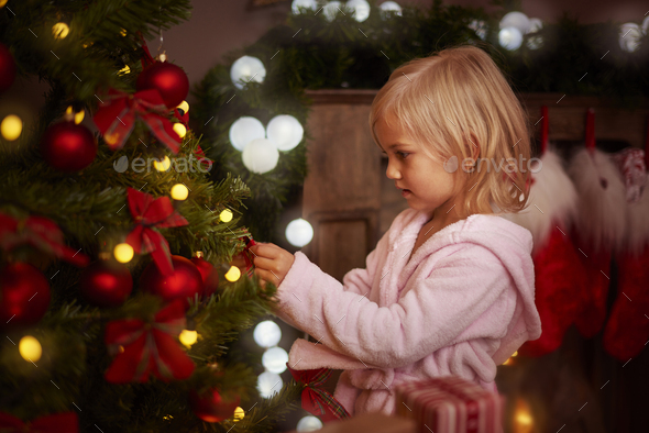 Little girl decorating a christmas tree - Stock Photo - Images