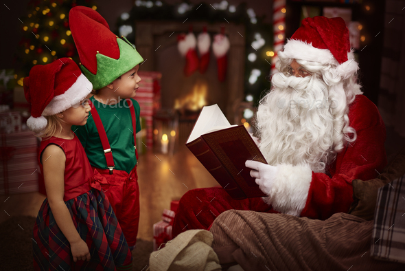 Mysterious santa claus reading a book with children - Stock Photo - Images
