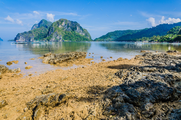 Stony beach during low tide in front of huge rocks in Background, El Nido, Palawan, Philippines - Stock Photo - Images
