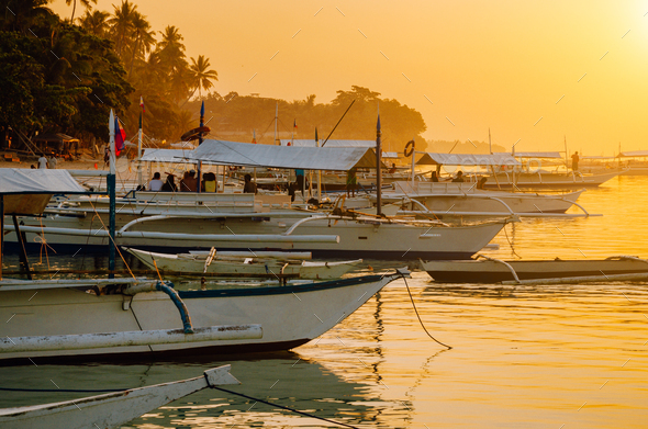 Sunset on the beach with silhouette of banca boat at Panglao Island, Bohol, Philippines - Stock Photo - Images