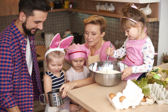 Children baking under watchful eye of parents - Stock Photo - Images