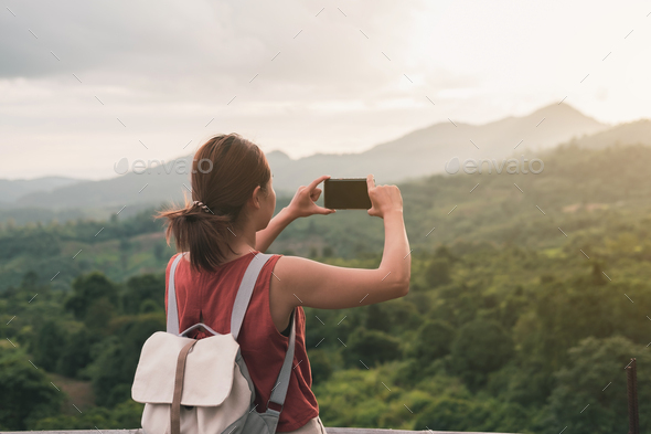 Young woman take a picture beautiful landscape with smartphone, Summer vacation and travel concept - Stock Photo - Images
