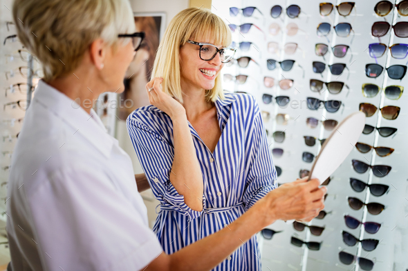 Beautiful young woman choosing new pair of spectacles in opticians store. Optics. Ophthalmology - Stock Photo - Images