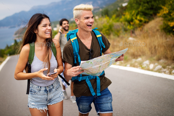 Adventure, travel, tourism and people concept - group of smiling friends with backpacks and map - Stock Photo - Images