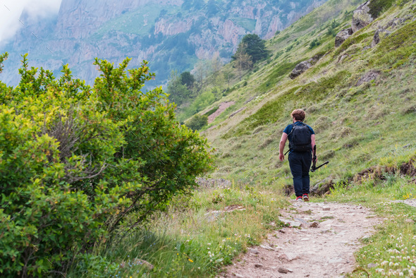 Back view male hiker walks in beautiful mountains in North Caucasus - Stock Photo - Images