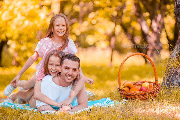 Happy father and little daughers relax by the lake - Stock Photo - Images