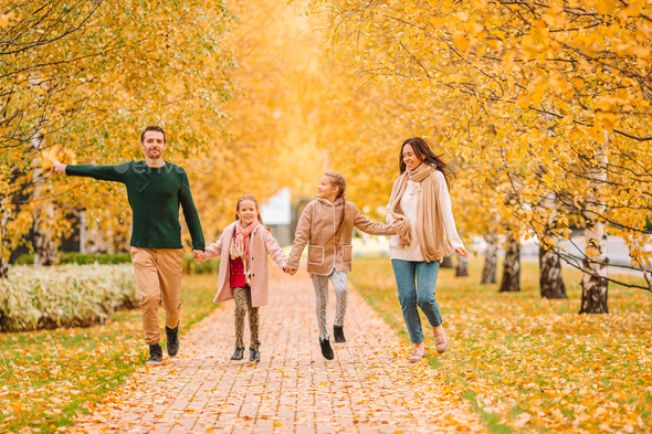 Portrait of happy family of four in autumn day - Stock Photo - Images