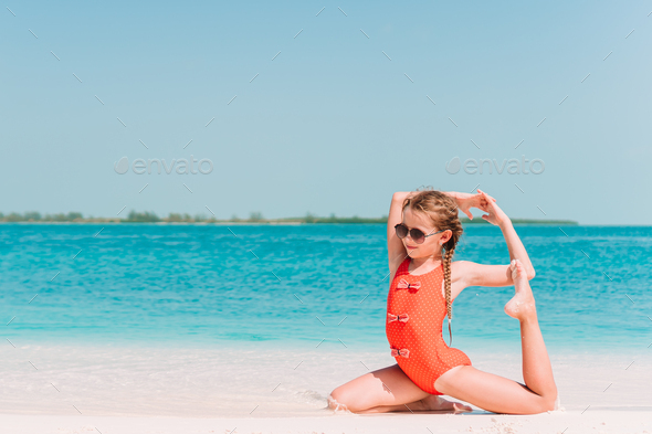 Adorable active little girl at beach during summer vacation - Stock Photo - Images