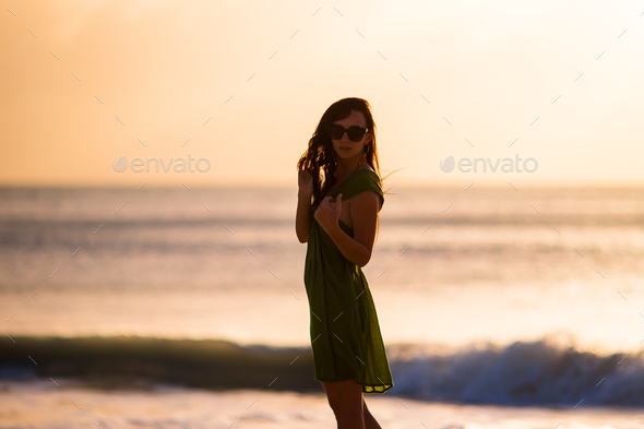 Beautiful woman on white beach at sunset - Stock Photo - Images