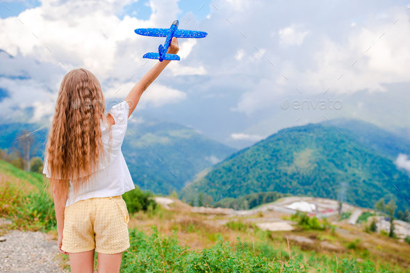 Happy little girl with toy airplane in hands in mountains - Stock Photo - Images